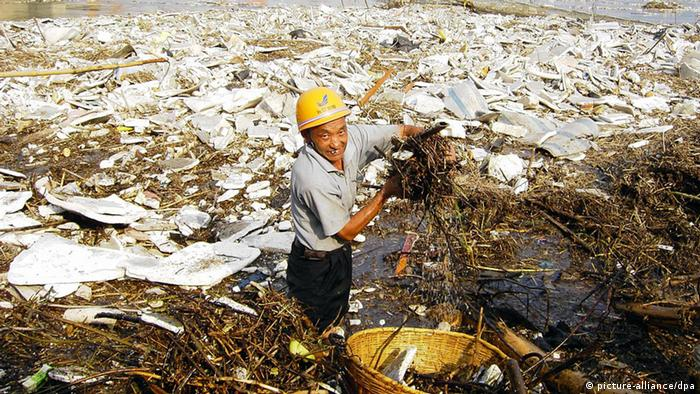 Man stands in a trash-filled river