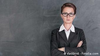Eine streng aussehende Lehrerin steht mit verschränkten Armen vor einer Tafel