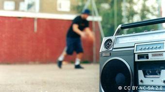 Im Vordergrund ist ein Ghettoblaster zu sehen, im Hintergrund spielt ein Junge Basketball.