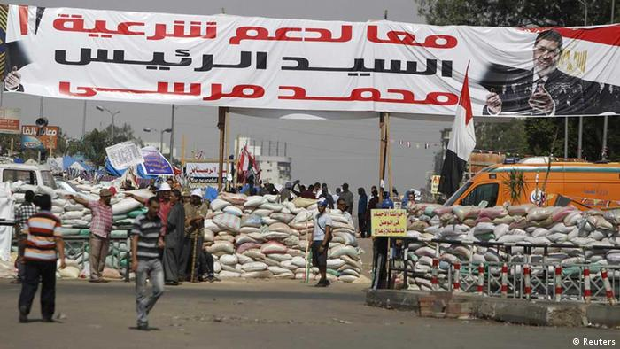 Members of the Muslim Brotherhood and supporters of deposed Egyptian President Mohamed Morsi stand guard in front of sandbags placed at the entrance to their camp near the Tomb of the Unknown Soldier, close to Rabaa Adawiya Square, where they are camping in Nasr city area, east of Cairo August 1, 2013. Photo: REUTERS/Amr Abdallah Dalsh