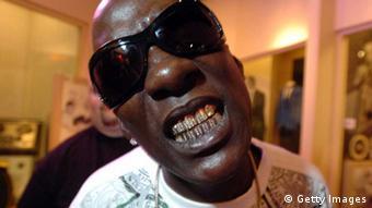 Ein dunkelhäutiger Mann schaut mit Sonnenbrille in die Kamera und zeigt dabei seine glitzernde Zahnschiene.