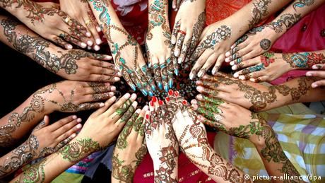 Pakistanische Mädchen strecken ihre bemalten Unterarme aus - Foto: dpa
