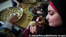 A Palestinian decorates traditional biscuits popular on the occasion of Eid al-Fitr at her home in the West Bank city of Ramallah, on August 5, 2013. Muslims around the world are preparing to celebrate the Eid al-Fitr holiday, which marks the end of the fasting month of Ramadan. Preparations include buying new clothes, toys and special sweets. AFP PHOTO/ABBAS MOMANI (Photo credit should read ABBAS MOMANI/AFP/Getty Images)