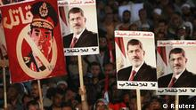 Supporters of deposed Egyptian President Mohamed Mursi hold up posters, including Egypt's army chief General Abdel Fattah al-Sisi (L) that reads, A murderer, during a protest at the Rabaa al-Adawiya square where they are camping, in Cairo, August 6, 2013. The chances for a negotiated end to Egypt's political crisis looked to have hit the rocks on Tuesday with the army-installed government reportedly ready to declare that foreign mediation efforts had failed. It would also declare that Muslim Brotherhood protests against the army's overthrow of Mursi were non-peaceful - a signal that the government intends to end them by force. The posters of Mursi read, Yes to legitimacy, no to the coup. REUTERS/Mohamed Abd El Ghany
