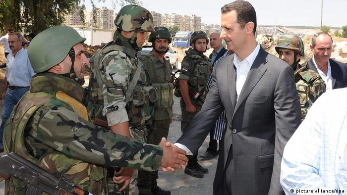 epa03810365 A handout photo made available by the official Syrian Arab News Agency (SANA) shows Syrian President Bashar Assad (R) inspecting a unit of the Syrian armed troops in the Damascus suburb of Darayya, Syria, 01 August 2013. The visit came on the occupation of the Army Foundation Day. The city has witnessed fierce clashes over the past months between the Syrian army troops and armed groups. EPA/SANA / HANDOUT HANDOUT EDITORIAL USE ONLY/NO SALES