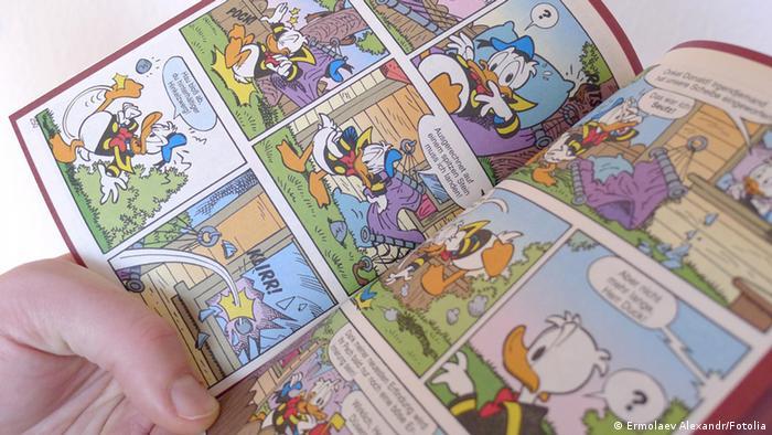 Ein Mann liest in einem Donald Duck-Comic