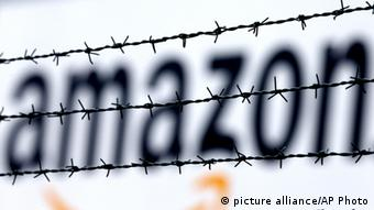 The internet trader Amazon logo is seen behind barbed wire at the company's logistic center in Rheinberg,Germany, Tuesday, Feb.19, 2013. Amazon is in trouble after a TV report on inhuman working conditions in Germany. (AP Photo/Frank Augstein)