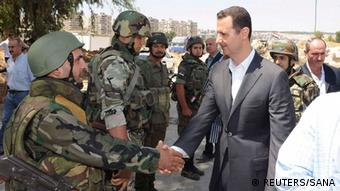 Syria's President Bashar al-Assad (R) shakes hands with a member of a military personnel during his visit to a military site in the town of Daraya, southwest of Damascus, on the 68th anniversary of army day, in this handout photograph distributed by Syria's national news agency SANA on August 1, 2013. Assad said on Thursday he was confident of victory against rebels and made a symbolic visit to the town once overrun by insurgents but now mostly retaken by his army. REUTERS/SANA/Handout via Reuters (SYRIA - Tags: ANNIVERSARY CIVIL UNREST MILITARY POLITICS CONFLICT) ATTENTION EDITORS - THIS IMAGE HAS BEEN SUPPLIED BY A THIRD PARTY. IT IS DISTRIBUTED, EXACTLY AS RECEIVED BY REUTERS, AS A SERVICE TO CLIENTS. FOR EDITORIAL USE ONLY. NOT FOR SALE FOR MARKETING OR ADVERTISING CAMPAIGNS