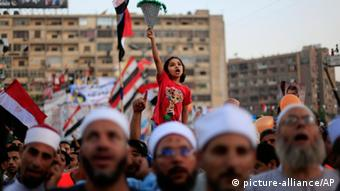 An Egyptian girl chants slogans as she joins supporters of Egypt's ousted President Mohammed Morsi as they celebrate the first day of the Eid al-Fitr holiday, marking the end of the Muslim holy fasting month of Ramadan outside Rabaah al-Adawiya mosque, where protesters have installed a camp and hold daily rallies in Nasr City, Cairo, Egypt, Wednesday, Aug. 8, 2013. This year's holiday of Eid al-Fitr was overshadowed by the deep divisions in Egypt, with the interim government planning to celebrate the festival with outdoor prayers in town center squares and Morsi's supporters marking the holiday with their own protest gatherings, including the two major sit-in by the Islamists in Cairo. (AP Photo/Khalil Hamra)