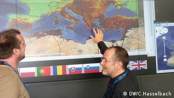 Billing und ein Kollege stehen an der Karte. Foto: Christoph Hasselbach (DW)