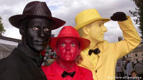 People dressed in black, red, yellow (picture-alliance/dpa)