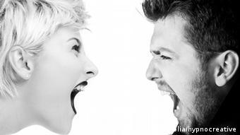 Eine Frau (links) und ein Mann schreien sich mit weit geöffnetem Mund an