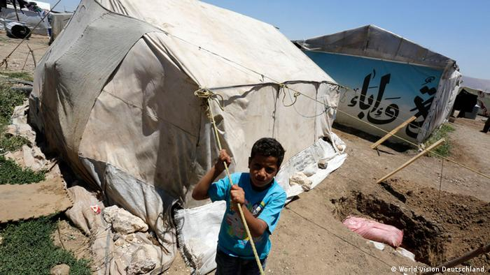 Standing before a tent, a ragged-looking boy of Middle-Eastern descent looks at the camera. (Photo: World Vision Deutschland)