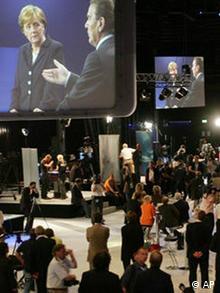 Journalisten verfolgen auf Bildschirmen das TV-Duell von Bundeskanzler Gerhard Schroeder, rechts, und der CDU-Vorsitzenden Angela Merkel in einem Pressezentrum in Berlin