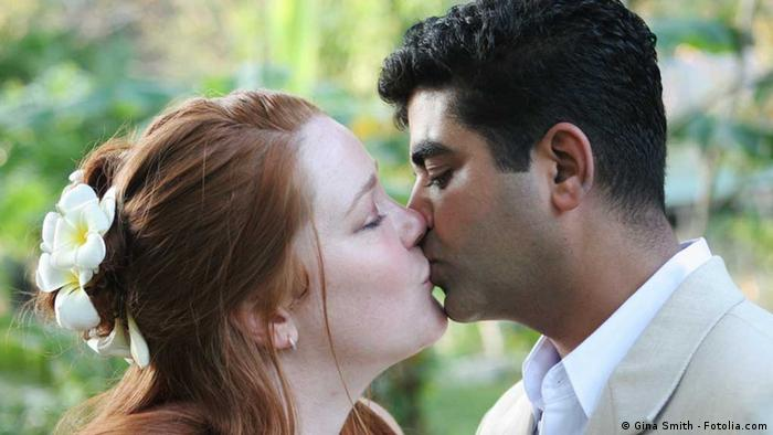 A bride with light skin and red hair kisses a dark-skinned groom with black hair. (Photo: Gina Smith)