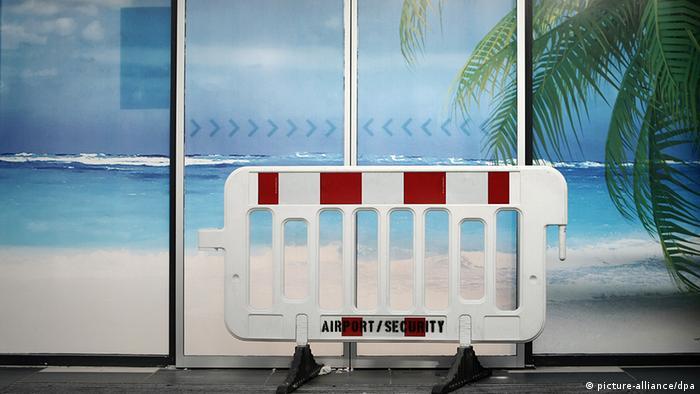 Eine Absperrung der Flughafen-Sicherheit versperrt im Flughafen in Frankfurt am Main den Durchgang durch eine mit einem Strandfoto beklebte Tür (Foto: pa/dpa)