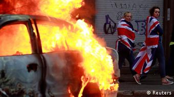 Women draped in Union flags walk past a burning car after loyalist protesters attacked the police with bricks and bottles as they waited for a republican parade to make its way through Belfast City Centre August 9, 2013 (Photo: REUTERS/Cathal McNaughton)
