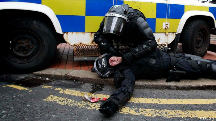 A police officer is tended to by a colleague after Loyalist protesters attacked the police with bricks and bottles as they waited for a republican parade to make its way through Belfast City Centre, August 9, 2013. Police fired plastic bullets and water cannon at rioters in the heart of Belfast on Friday after being pelted by missiles for the second successive night in the latest bout of Northern Ireland's sporadic sectarian violence. Police said two officers were injured. Eight were hurt the previous night when a crowd threw paint bombs, bottles and masonry at police. REUTERS/Cathal McNaughton (NORTHERN IRELAND - Tags: CIVIL UNREST CRIME LAW TPX IMAGES OF THE DAY)