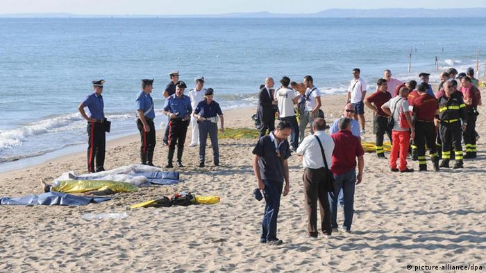 epa03818819 Italian police stands next to bodies of migrants at the beach in Plaia, near Catania, on the island of Sicily, Italy, 10 August 2013. Six migrants have died making the sea crossing from North Africa to Italy, the Italian authorities said on 10 August. The six men were among a group of some 120 people - including women and children - whose fishing boat arrived at Catania in eastern Sicily. EPA/ORIETTA SCARDINO