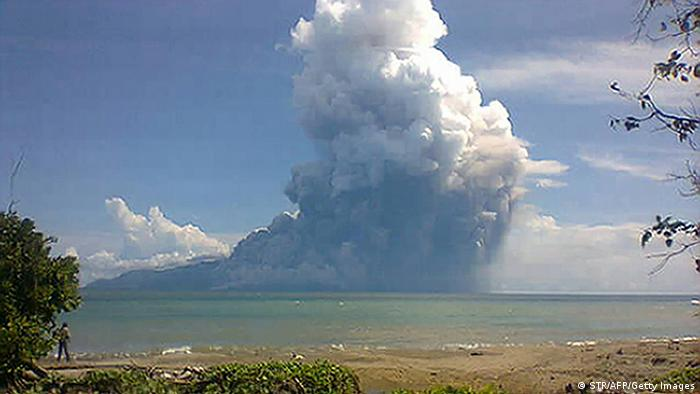 The photo taken from the Maurole district of East Nusa Tenggara province with a camera phone shows Mount Rokatenda volcano spewing a huge column of hot ash during an eruption on August 10, 2013. The volcano erupted in central Indonesia on August 10, spewing hot ash and rocks high into the air and killing five people, an official said. Mount Rokatenda, on the tiny island of Palue, sent fast-moving red-hot ash onto a nearby beach, leaving three adults and two children dead, said vulcanology centre head Surono. AFP PHOTO (Photo credit should read STR/AFP/Getty Images)