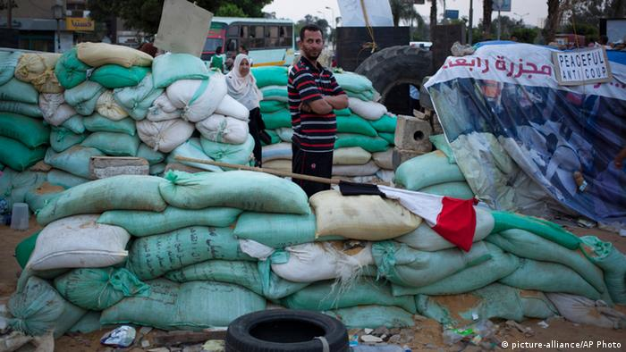 A supporter of Egypt's ousted President Mohammed Morsi stands guard by sand barriers that have set up by supporters of Morsi to install a camp and hold daily rallies outside Rabaah al-Adawiya mosque, in Cairo, Egypt, Saturday, Aug. 10, 2013. (AP Photo/Khalil Hamra)