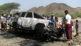 People of Middle Eastern descent surround the burned-out shell of a white vehicle, with mountains in the background.