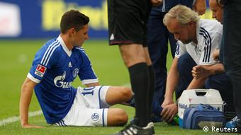 A doctor looks at an injury of Schalke 04's Julian Draxler (L) during the German first division Bundesliga soccer match against Hamburg SV in Gelsenkirchen August 11, 2013. REUTERS/Ina Fassbender (GERMANY - Tags: SPORT SOCCER HEALTH) DFL RULES TO LIMIT THE ONLINE USAGE DURING MATCH TIME TO 15 PICTURES PER GAME. IMAGE SEQUENCES TO SIMULATE VIDEO IS NOT ALLOWED AT ANY TIME. FOR FURTHER QUERIES PLEASE CONTACT DFL DIRECTLY AT + 49 69 650050