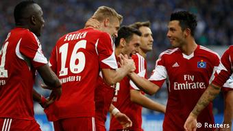 Hamburg SV's Lasse Sobiech (2nd L) and team mates celebrate a goal against Schalke 04 during the German first division Bundesliga soccer match in Gelsenkirchen August 11, 2013. REUTERS/Ina Fassbender (GERMANY - Tags: SPORT SOCCER) DFL RULES TO LIMIT THE ONLINE USAGE DURING MATCH TIME TO 15 PICTURES PER GAME. IMAGE SEQUENCES TO SIMULATE VIDEO IS NOT ALLOWED AT ANY TIME. FOR FURTHER QUERIES PLEASE CONTACT DFL DIRECTLY AT + 49 69 650050