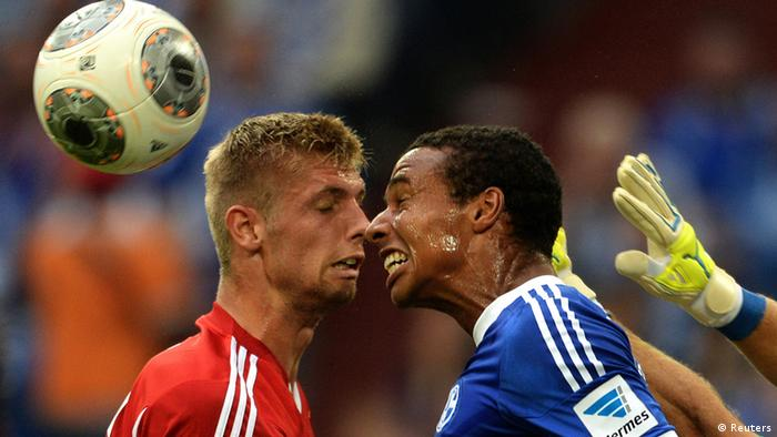 Hamburg's Lasse Sobiech and Schalke's Joel Matip clash heads going for the ball in their 11.08.13 match in Gelsenkirchen.