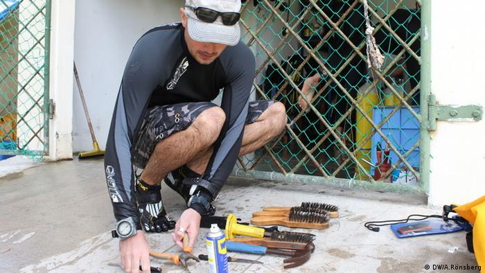 Chris, a volunteer from the UK, cleaning wire brushes after cleaning ropes in the coral nursery(copyright: Andrea Rönsberg)