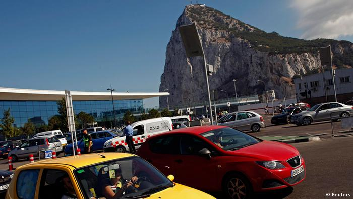 Drivers wait in line on a hot summer day to enter to Spain at its border with the British territory of Gibraltar in front of the Gibraltar International airport (L) and the Rock (rear) in Gibraltar, south of Spain August 9, 2013. Spanish Prime Minister Mariano Rajoy on Friday threatened unilateral measures in a spat with Gibraltar over fisheries although he also said he hoped for talks soon with Britain about the disputed territory. REUTERS/Jon Nazca (GIBRALTAR - Tags: POLITICS TRANSPORT)