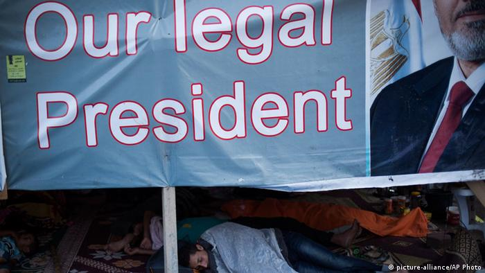Banner with photo of Morsi reading Our legal president (photo: AP Photo/Manu Brabo)