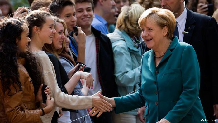 German Chancellor Angela Merkel (R) shakes hands with pupils as she arrives for a visit at the Heinz Schliemann grammar school in Berlin August 13, 2013. (Photo: REUTERS/Thomas Peter)