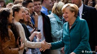 German Chancellor Angela Merkel (R) shakes hands with pupils in Berlin August 13, 2013.