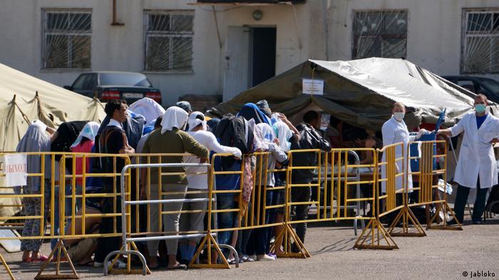 Очередь мигрантов, ожидающих получения своей порции обеда.
