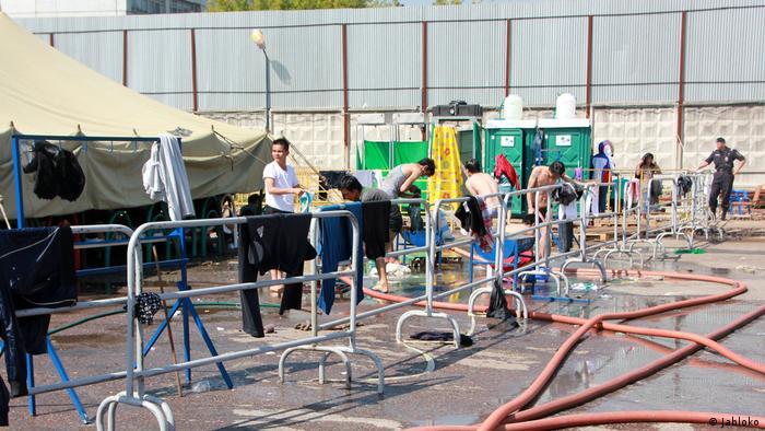 Мигранты поливают себя из шлангов в лагере в Гольяново