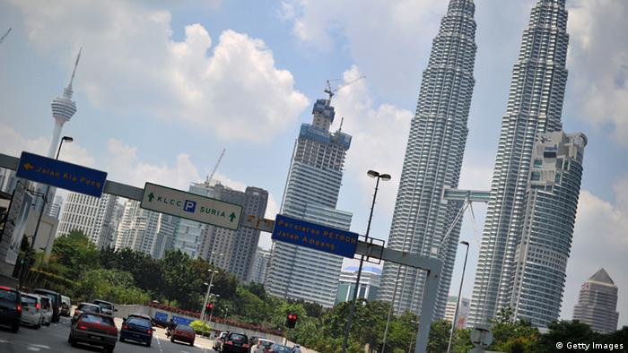 Traffic signs in front of Malaysia's iconic landmark Patronas Twin Towers point to different streets in downtown Kuala Lumpur on February 8, 2011. AFP PHOTO/ Saeed Khan (Photo credit should read SAEED KHAN/AFP/Getty Images)