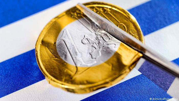 Scissors cutting through a euro coin to symbolize Greek haircut
