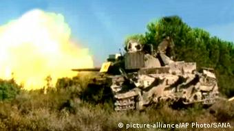 In this image released by the Syrian official news agency SANA, a Syrian forces tank fires during a battle against the Syrian rebels at an unidentified location (AP Photo/SANA)