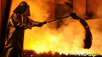 A worker at a steel factory against the fire of the furnace Photo: Julian Stratenschulte dpa/lni