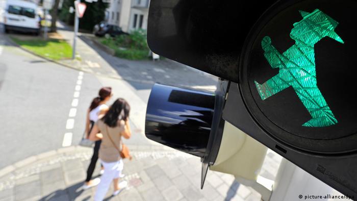 Two people cross a street, focus is on East Germany's little traffic light man