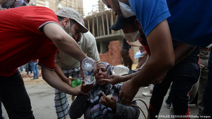 Egyptians help a woman suffering from tear gas exposure after canisters were fired by Egyptian police as they try to disperse a pro-Morsi camp in a street leading to Rabaa al-Adawiya in Cairo on August 14, 2013. Photo: KHALED DESOUKI/AFP/Getty Images