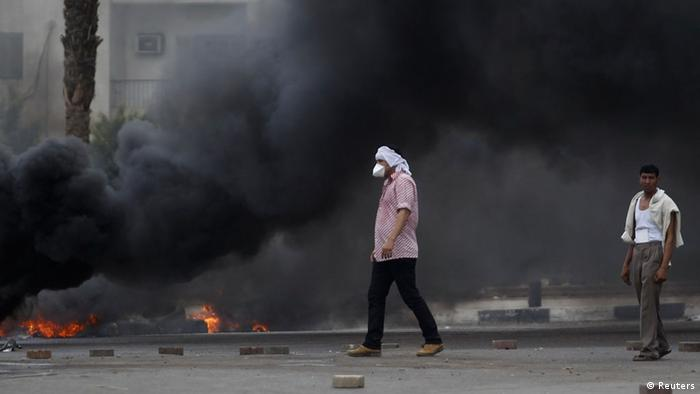 Members of the Muslim Brotherhood and supporters of deposed Egyptian President Mohamed Mursi walk near smoke from a fire at Rabaa Adawiya square, where they are camping, in Cairo August 14, 2013. (Photo: REUTERS/Amr Abdallah Dalsh)