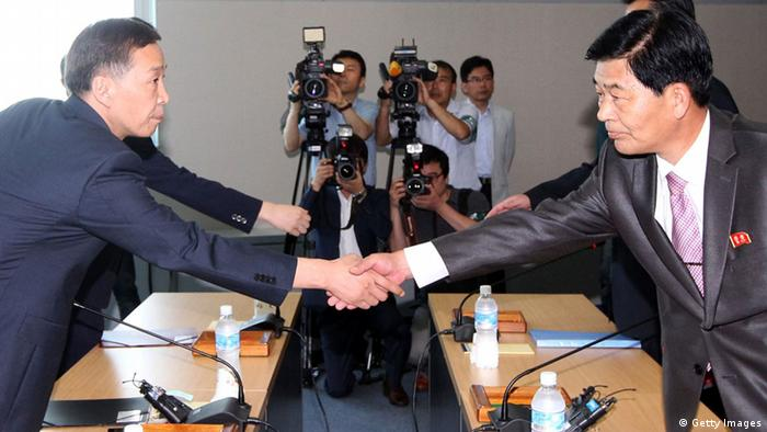 Kim Ki-Woong (L), the head of South Korea's working-level delegation shakes hands with his North Korean counterpart Park Chol-Su (R) during their meeting at Kaesong Industrial District Management Committee on August 14, 2013 in Kaesong, North Korea. (Photo by Lee Seung-Hwan-Korea Pool/Getty Images)