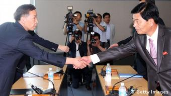 KAESONG, NORTH KOREA - AUGUST 14: (SOUTH KOREA OUT) Kim Ki-Woong (L), the head of South Korea's working-level delegation shakes hands with his North Korean counterpart Park Chol-Su (R) during their meeting at Kaesong Industrial District Management Committee on August 14, 2013 in Kaesong, North Korea. North Korea withdrew over 50,000 of its staff from the factories owned by Seoul in April of this year, and South Korea removed managers in May, during the height of tensions between the two nations. (Photo by Lee Seung-Hwan-Korea Pool/Getty Images)