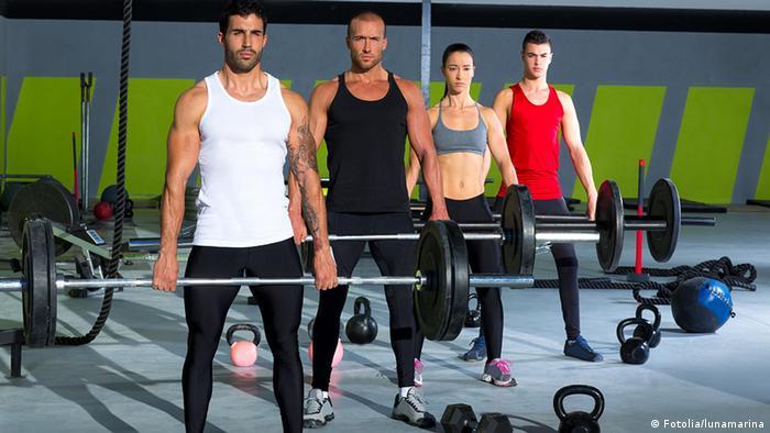 Drei Männer und eine Frau stehen in einer Sporthalle und halten Gewichtheberstangen in den Händen.