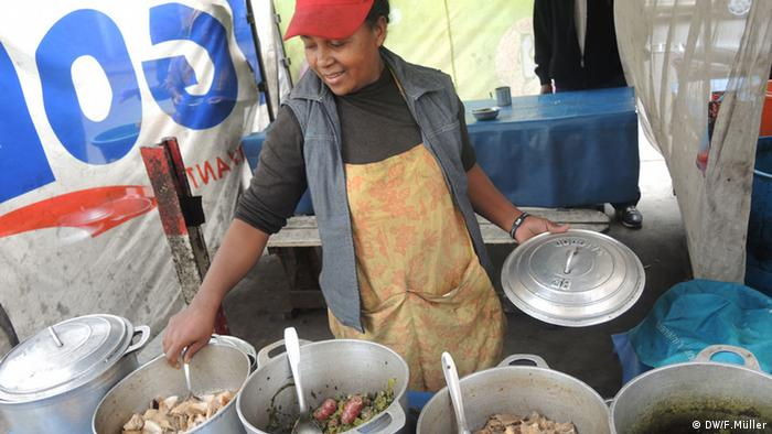Eine Frau verkauft an ihrem Stand am Straßenrand in Madagaskars Hauptstadt Antananarivo Reis, Fleisch und Gemüse (Foto: Friederike Müller/DW)