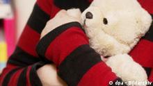Eine Frau hält einen Teddybär in ihren Armen. (Aufnahme vom 7.2.2003). Schlagworte Gesellschaft, Spielwaren, Symbole, Plüschtier, teddy, teddybär, biologische_Uhr, kinderlosigkeit, Unfruchtbar, trauer, einsamkeit