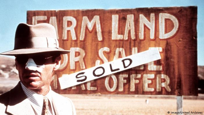 Jack Nicholson steht mit Hut, Sonnenbrille und verbundener Nase vor einem Schild mit der Aufschrift Farm Land For Sale - Sold in Polanskis Chinatown. (Film: Chinatown) (imago/United Archives)