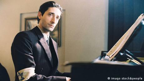 Adrien Brody sitzt in Polanskis Der Pianist mit Anzug und Judensternbinde am Klavier. (Film: Der Painist) (imago stock&people)